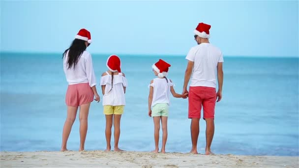 Happy family with two kids in Santa Hat on summer vacation celebrate Christmas
