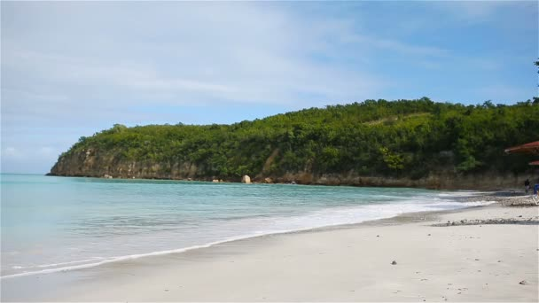 Idyllic tropical Carlisle bay beach with white sand, turquoise ocean water and blue sky at Antigua island
