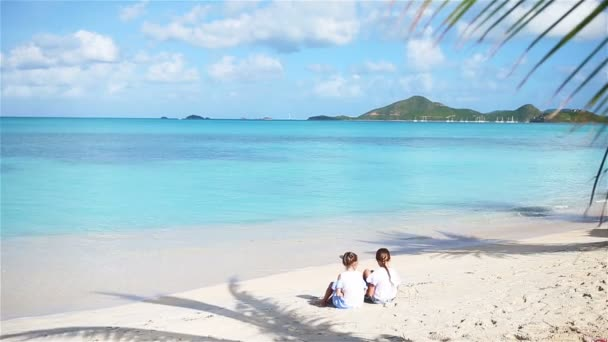 Two little girls on sandy beach. Happy kids sitting under the palm tree on tropical beach
