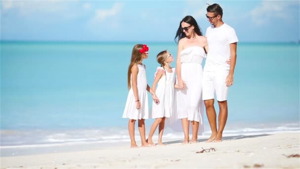 Young family walking on white tropical caribbean beach