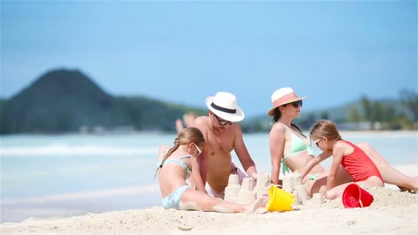 Family making sand castle and enjoying holidays at tropical white beach