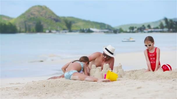 Otec a dvě dívky si hrají s pískem na tropické pláži