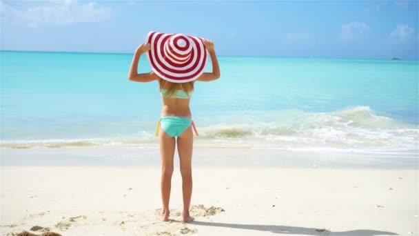 Roztomilá holčička v klobouku na pláži během karibské dovolené