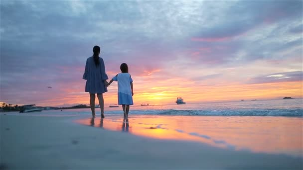 Little girl and daddy silhouette in the sunset at the beach