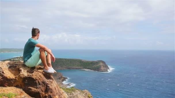 Young man enjoying breathtaking views from Shirley Heights on Antigua island