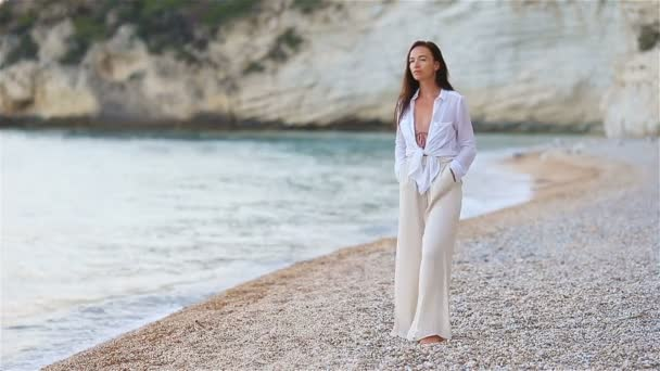 Young beautiful woman on white tropical beach.