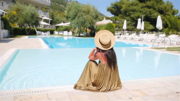Žena relaxace u bazénu v luxusním hotelovém resortu těší perfektní dovolenou na pláži