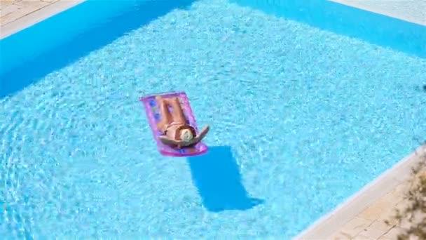 Fiatal nő bikini gumimatrac a nagy medence