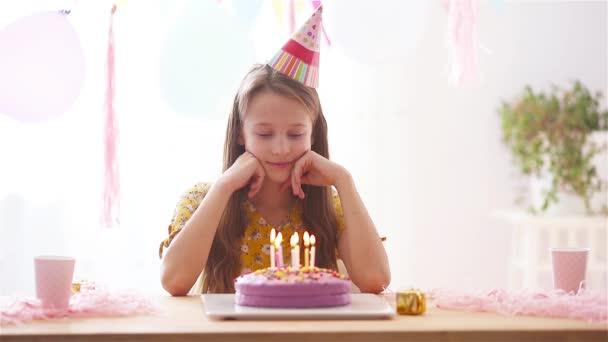 A kaukázusi lány álomszép mosollyal néz a szülinapi szivárvány tortába. Ünnepi színes háttér lufikkal. Születésnapi party és kívánságok koncepció.