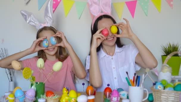 Matka a její dcera malují vajíčka. Šťastná rodina se připravuje na Velikonoce.