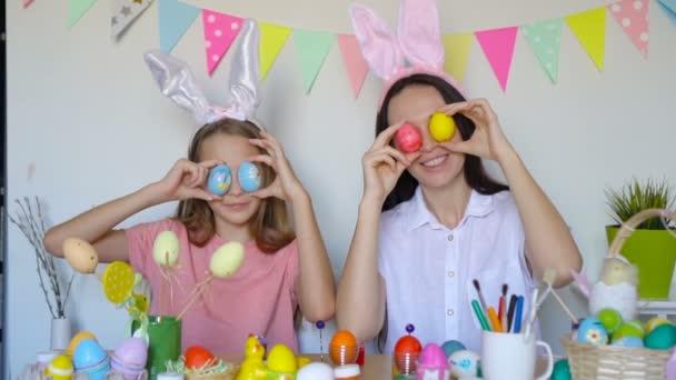 Anya és a kislánya tojásokat festenek. Boldog családi felkészülés húsvétkor.