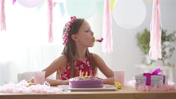 Běloška se zasněně usmívá a dívá se na narozeninový duhový dort. Slavnostní barevné pozadí s balónky. Koncept narozeninové oslavy a přání.