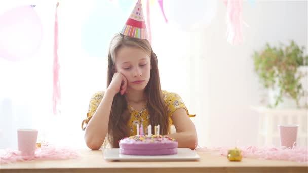 Kaukázusi lány kiábrándító a születésnapján. Ünnepi színes háttér lufikkal. Születésnapi party és kívánságok koncepció.