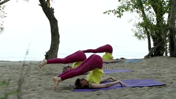 Ženy dělají jógu rohože na pláži
