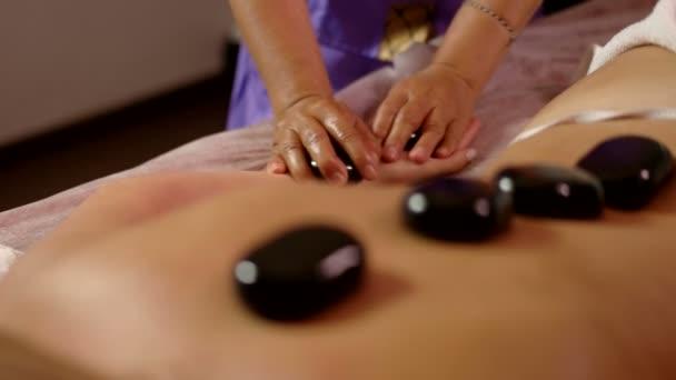 Masér dělá masáž lávovými kameny