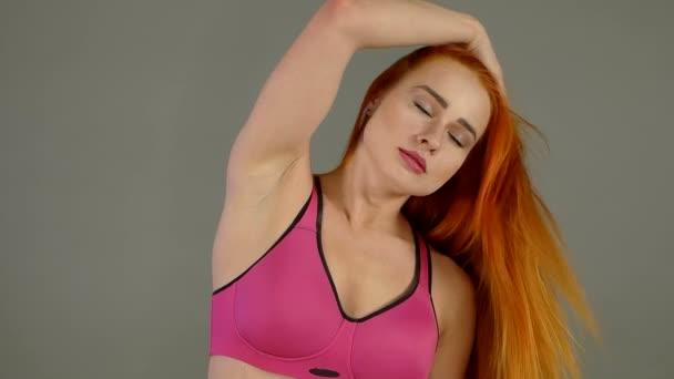 Sexy dívka se dotýká zrzavé vlasy v pomalém pohybu