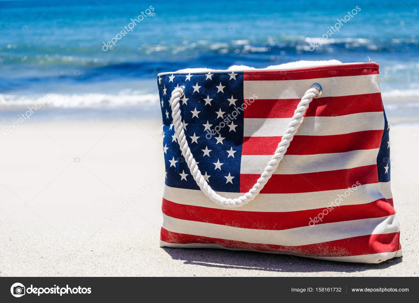 Borsa con i colori della bandiera americana vicino oceano sulla ...