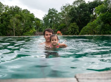 Portrait of Father and daughter enjoying a summer holiday in swimming pool at Northern resort of Thailand.