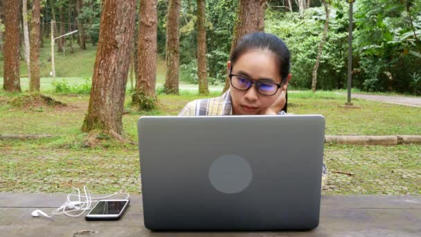 Happy casual beautiful woman working on laptop while sitting in national park.