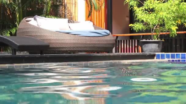 Water ripple in the swimming pool and Relaxing chair with pillow by the poolside on sunshine day.