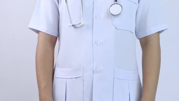 Young woman doctor in white coat with her hands in pockets on a white background.
