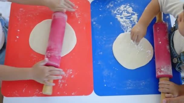 Šťastné děti připravují těsto na domácí pizzu v kuchyni, rozválejí těsto s válečkem a moukou na stole. Rodinná zábava a vaření koncept.