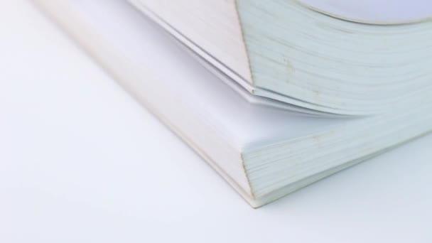 Detailní záběr Obrácení stránek knihy na bílém stole.