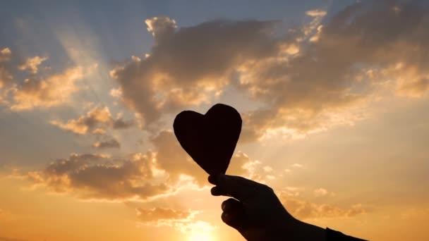 Silueta srdce ve tvaru lepenky v ruce a slunce svítí srdcem na pozadí západu slunce. Koncepty lásky a Valentýna.