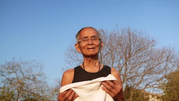 Happy elderly man wiping sweat using white towel after workout in park. Healthcare concept.