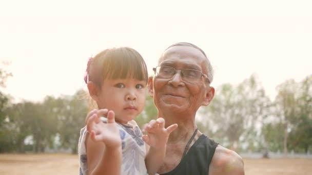 Portrét šťastného dědečka a vnučky se usmívají, dívají se do kamery v letním parku. Koncept rodinného vztahu.