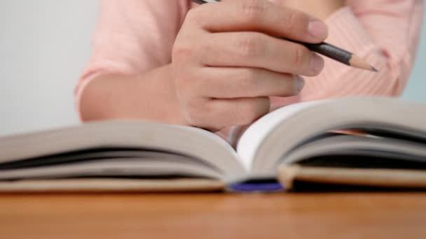 Közelkép a nő kezét rajz egy vonalat, és írjon rövid összefoglalót olvasás közben egy könyvet a könyvtárban.