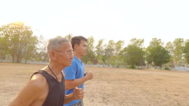 Asian senior man jogging with adult son in the summer park. Happy family spending free time together. Healthy lifestyle concept.