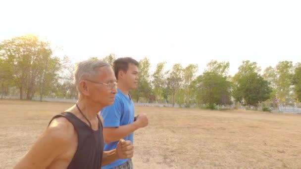 Ázsiai végzős férfi kocog a felnőtt fiával a nyári parkban. A boldog család együtt tölti a szabadidejét. Egészséges életmód koncepció.