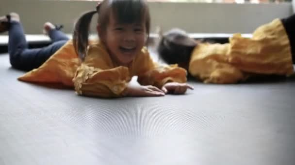 Adorable little child girl having fun to play on trampoline in playground. Concept of happy family and childhood.