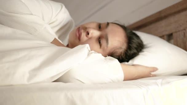 Unavená asijská žena pokrytá bílou dekou ležící v posteli v den dovolené.