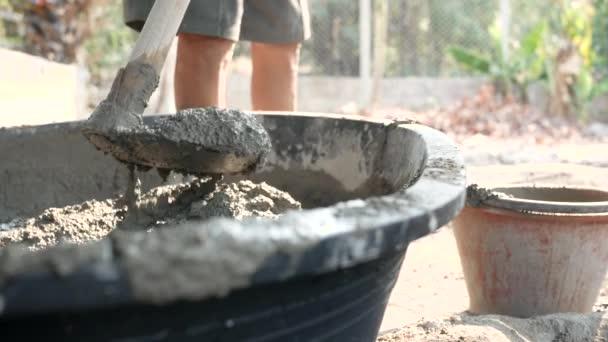Stavební dělník nebo sádrokarton nabírá smíšený beton do kbelíku na staveništi. Koncept stavby.