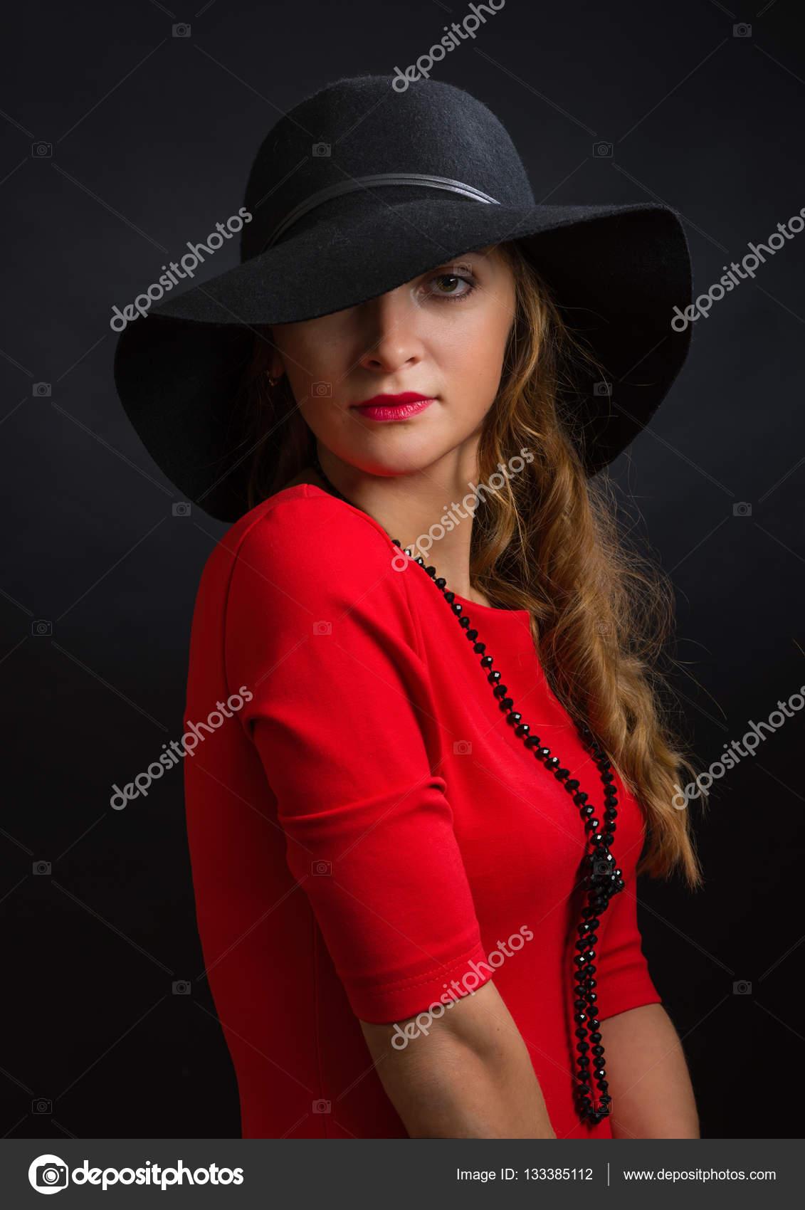 419ae67139db La bella ragazza in un vestito rosso luminoso e cappello nero con vasti  campi– immagine stock