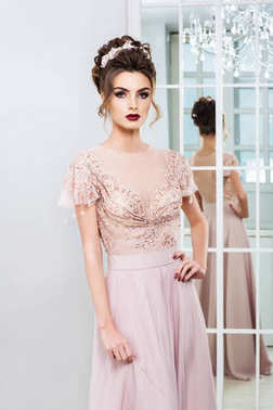 portrait of fashion woman with hairstyle in beautiful dress near mirror