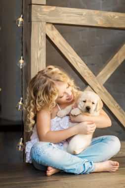 cute little girl hugging adorable puppy sitting on wooden floor