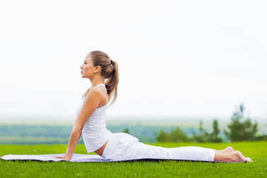 portrait of young slim woman exercising on yoga mat outdoor, healthy lifestyle, yoga and sport concept