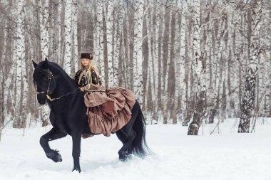 Little girl is riding a friesian horse, outdoor