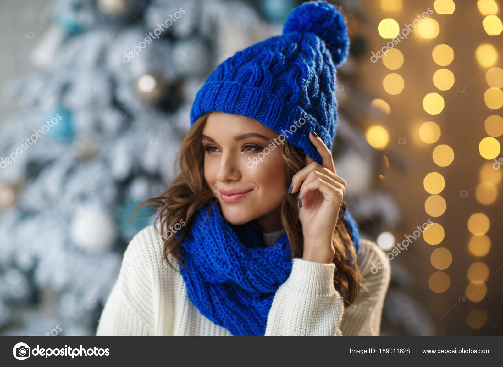 Giovane donna graziosa in cappello di lana blu e sciarpa che propone sulla  priorità bassa dell albero di Natale innevato — Foto di ... dc561796d1b9