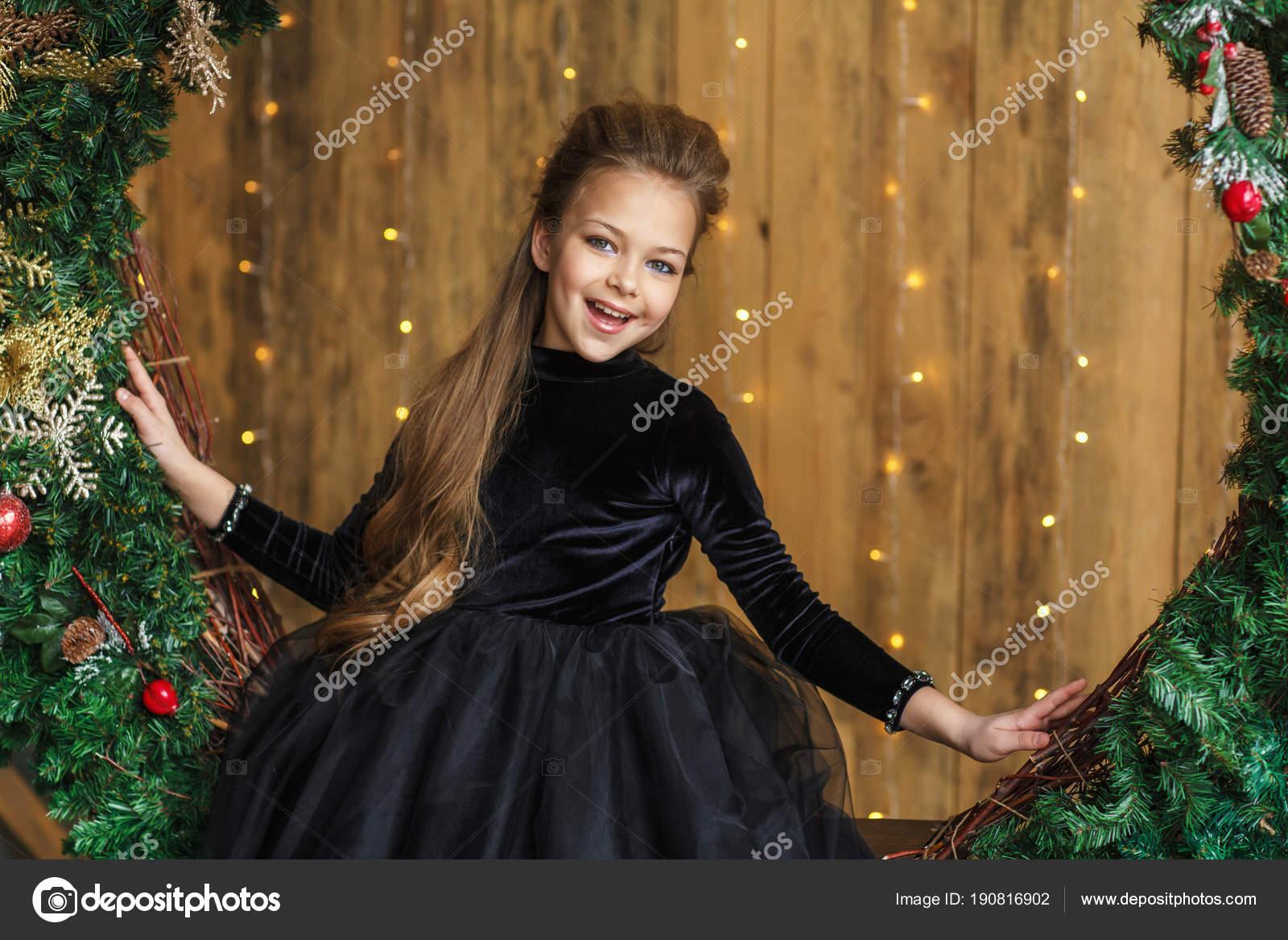 Vonzó Kis Lány Fekete Ruha Egy Karácsonyi Koszorú — Stock Fotó ... 28fc7df5e7