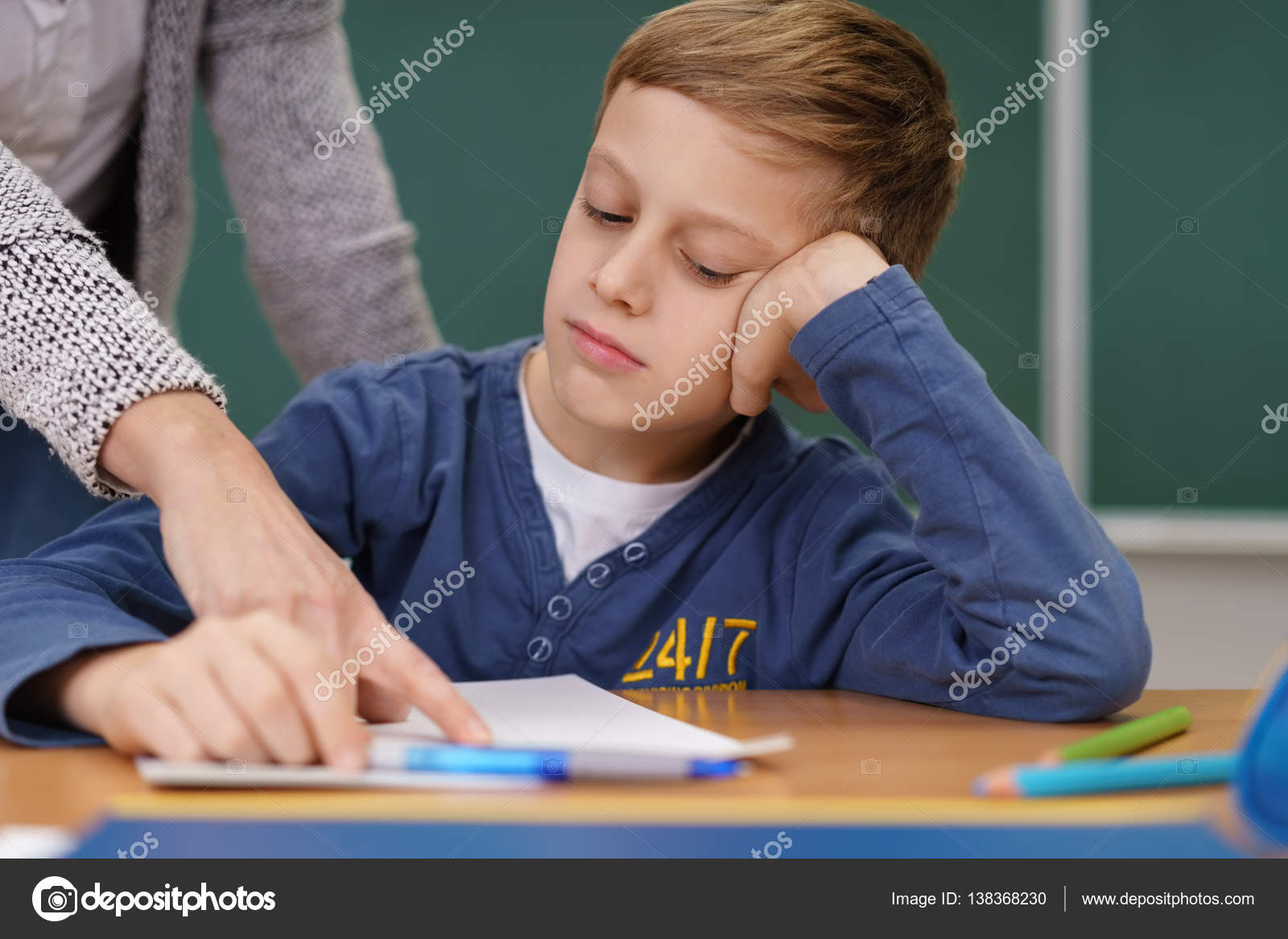 the youngster sitting behind the teachers desk