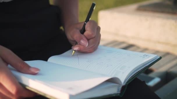 Üzletasszony dolgozik, jegyzetel egy jegyzetfüzetben. A nő kézzel ír. Koncentrálj az írásra a jegyzetfüzetben.