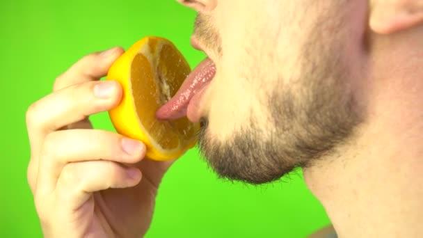 Mužský jazyk Lízání nakrájený pomeranč Imitace lízání na pozadí zelené obrazovky. Sexuální koncept. Sexuální pojídání ovoce.