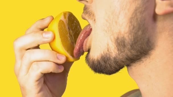 Male Tongue Licking Sliced Orange Imitating Cunnilingus on Yellow Background. Sex concept. Sexual Fruit Eating. Imitating oral sex