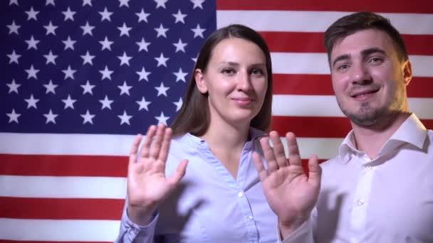 Šťastný Američan rodina pohledný muž a žena na americkém vlajkovém pozadí, usmívat se a mávat rukama. Americký rodinný koncept. Američtí vlastenci