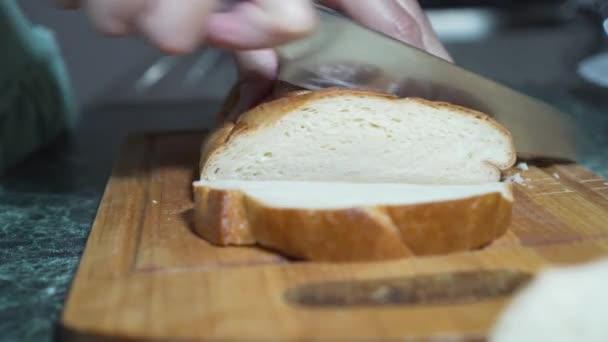 Nahaufnahme von Frauenhänden, die frisches, weiches Brot auf einem Holzbrett schneiden