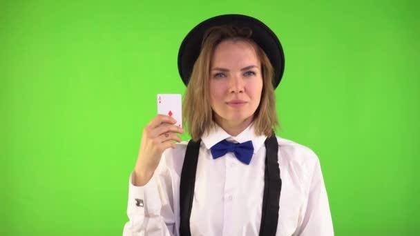 Croupiermädchen in weißem Hemd, Hut und Fliege zeigt Spielkarten und lächelt. Vier Ass-Karten, Mädchen zeigt ein Superzeichen. Grüner Hintergrund, chromakey